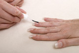 Applying clear nail varnish to acrylic finger nails poster