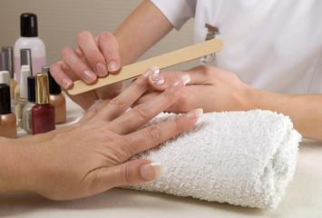 Manicurist filing clients finger nails