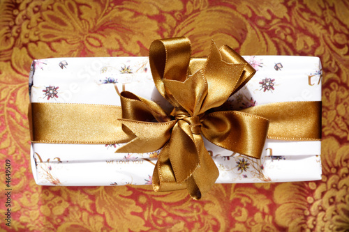 Gift box with a golden ribbon and bow.