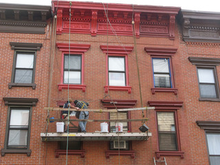 painting the window frames of a townhouse