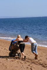 Two women pushing a pram on a beach