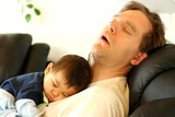 Father sleeping on chair with his baby boy on chest