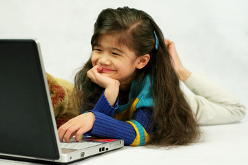FIve years old girl playing on the laptop