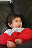 Happy eight months old baby sitting on couch laughing poster
