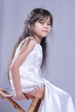 Little girl in satin dress posing quietly on a wooden stool poster