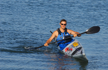 Athletic man showing off his mastery of kayaking