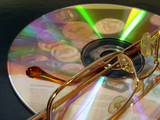laser disc with laing glasses and money coins reflections poster