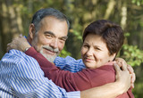 Happy elderly couple embracing outdoors poster