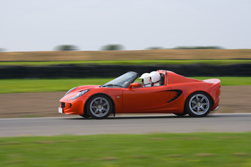 Bright red sports car at speed on a race circuit