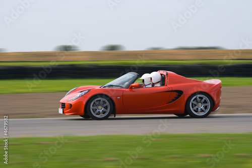 Foto op Canvas Snelle auto s Bright red sports car at speed on a race circuit
