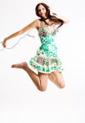 Young female jumping while listening to music