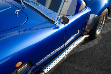 Blue classic American muscle car with chrome side exhaust