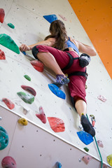 A woman on a climbing wall in an indoor climbing center.