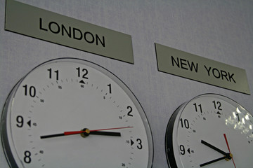 two clocks on the wall with different time zones