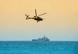 helicopter hovering over battleship - 4699594