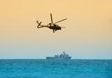 helicopter hovering over battleship poster