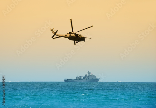 helicopter hovering over battleship