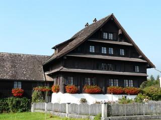 Mit Geranien geschmücktes Bauernhaus in Ibach (Schweiz)