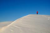 One man in red  wind-breaker trekking on a snow mountain. poster