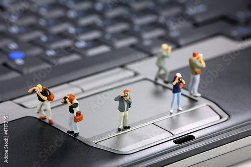 Miniature photographers or photojournalists on a laptop