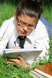 student with glasses studying outdoors, youth writing, poster