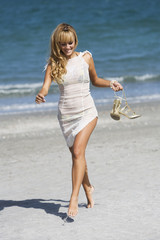 Pretty woman barefoot holding a pair of shoes