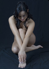 Beautiful nude woman on a black floor