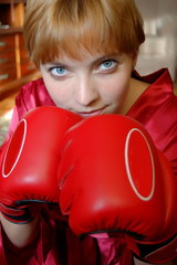 girl boxing with gloves in front and angry
