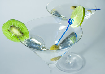 Cocktail glasses with olive, lime and kiwifruit