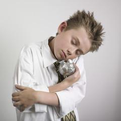 Boy cradling piggy bank