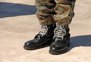 Feet of camouflaged soldier
