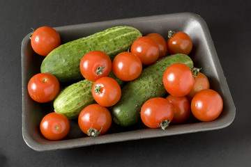 Tomatoes and cucumber in plastic container