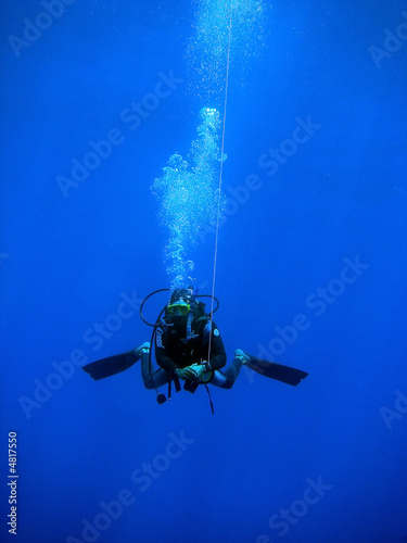 Diver swimming with buoy attached to rope - 4817550