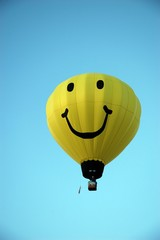 Big yellow happy face hot air balloon against bright blue sky