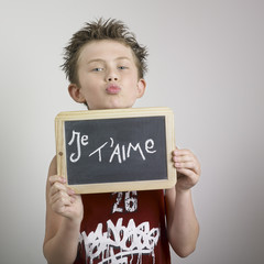 Boy holding je t'aime sign