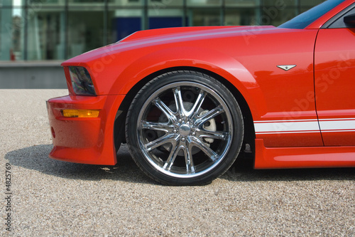 Foto op Plexiglas Motorsport Bright red American muscle car with building in background
