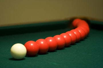 White cue ball in front of arcing red pool balls