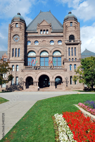 Ontario parliament building with red and white flowers
