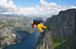base-jumper falling from cliff down to the fjord - 4840174
