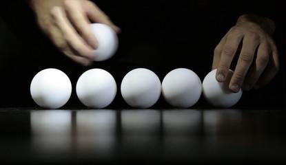 fila di palline bianche con mao che le sposta