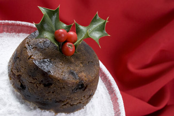 Christmas pudding with holly on dish dusted with icing sugar