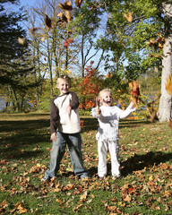 brother and sister throwing leafs
