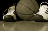 Basketball and shoes on hardwood court poster