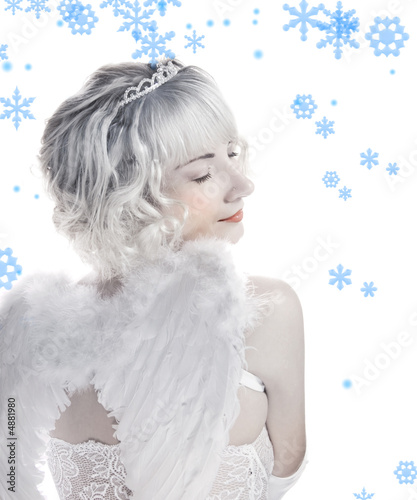 Blond angel girl with snowflakes around her