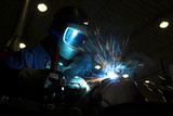 Welder welding a metal part in an industrial environment poster