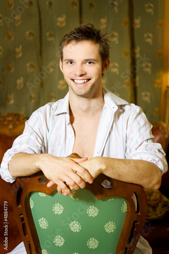 Rich handsome man sitting on chair