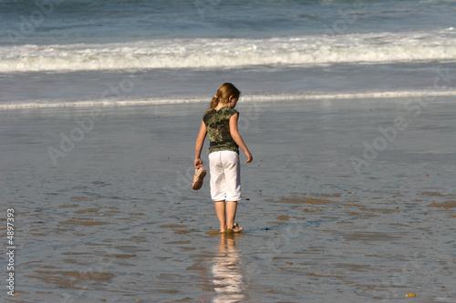 petite fille avec une queue de cheval qui regarde la mer