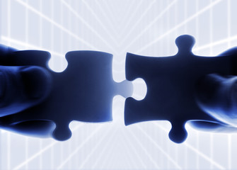 hands trying to fit two puzzle pieces together
