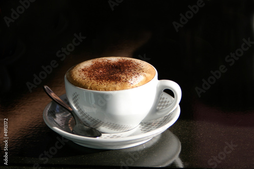 A cappuccino in a cup on a black table
