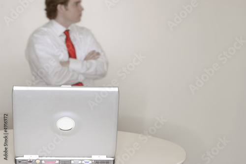 businessman standing behind laptop